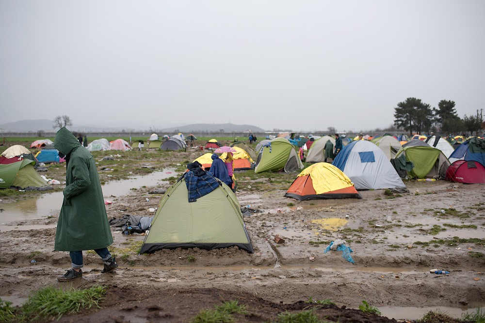 A man walks under the rain in a flooded muddy field near the transit camp of Idomeni, Greece. <br /> <br /> Thousands of refugees are stranded in Idomeni unable to cross the border. The facilities are stretched to the limit and the conditions are appalling.