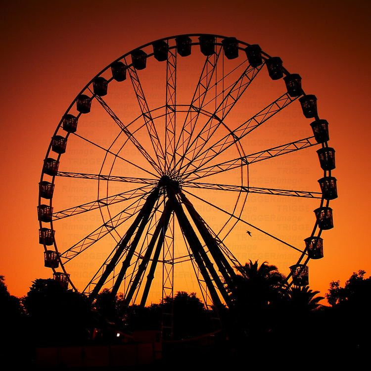 A large ferris wheel against an orange sunset