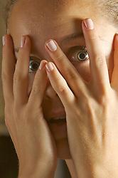 Mulher assustada olha entre os dedos.. FOTO: Jefferson Bernardes/Preview.com