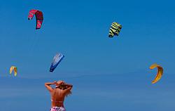 A sunbather adjust her swim suit as kitesurfing kites fill the sky. (Photo © Jock Fistick)