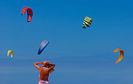 A sunbather adjust her swim suit as kitesurfing kites fill the sky. (Photo © Jock Fistick)