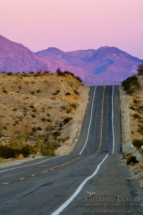 Sunrise on mountains over two lane desert road on a hill, Anza Borrego Desert State Park, San Diego County, California
