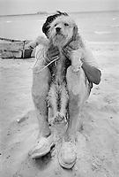 Man with dog on beach, Mexico