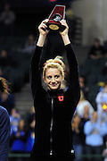 University of Utah freshman Mary Beth Lofgren hoists her trophy from the podium after tying for fifth place with Melissa Fernandez of the University of Illinois (not shown) at the 2011 Women's NCAA Gymnastics Championship Individual Event Finals on April 17, in Cleveland, OH. (photo/Jason Miller)