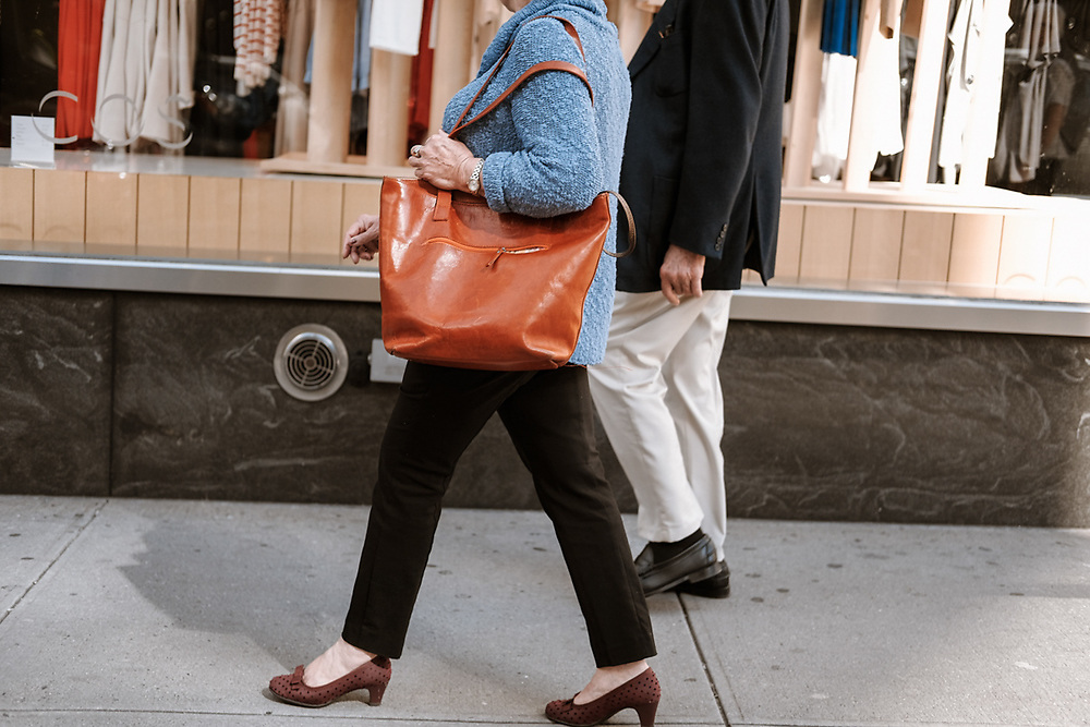 Couple walking on Bergenline Av. woman with rust color bag. West New York, NJ 2017