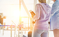 Portrait of man pushing baggage cart for check in with her daughter at airport