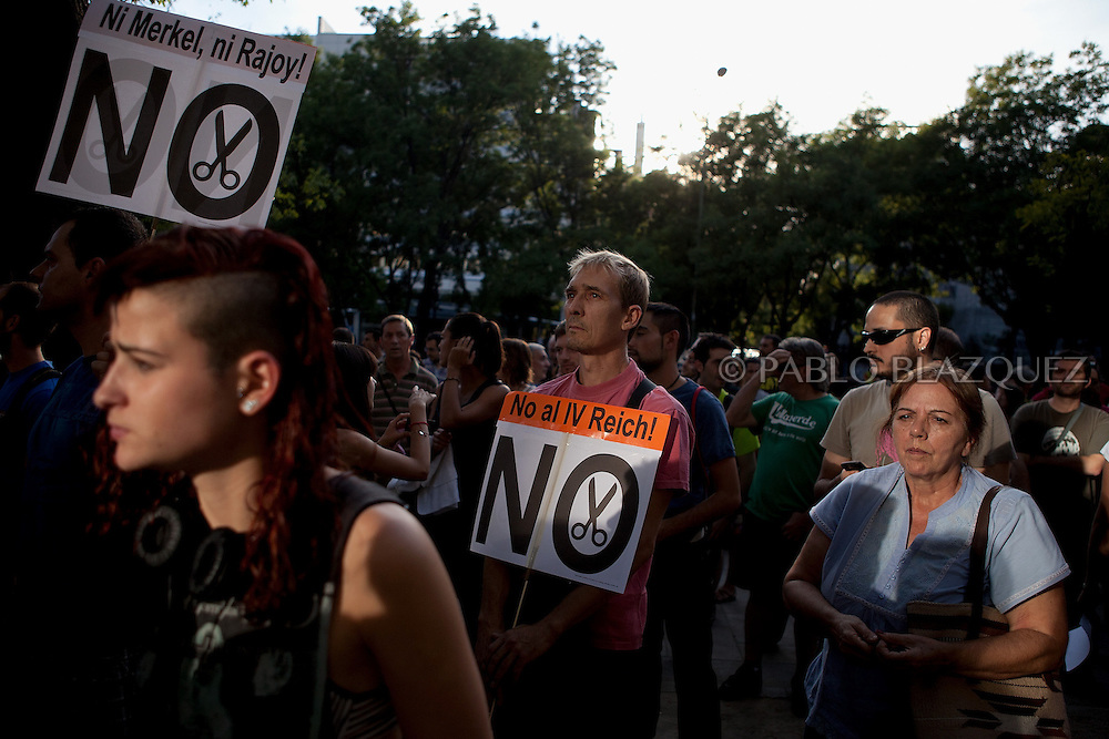 Protester hold a placards during a demonstration against German Chancellor Angela Merkel's official visit to Spain, in central Madrid on September 6, 2012. Placards reads 'No Merkel, No Rajoy, No Cuts' and 'No IV Reich!'. Merkel is in Spain for talks with conservative Spanish President Mariano Rajoy.