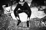 """""""Mehdi"""", jeune Tunisien, sur son lit dans l'un des tunnels du nord de Paris. Il vit sur la Petite Ceinture de manière aléatoire depuis plus d'un an."""