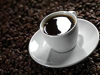 Cup of coffee with a saucer on coffee bean background