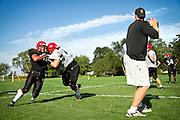 Matt John '12, left, attempts to rip past Jake McVeigh '11 during an offensive and defensive line drill during practice on Wednesday as Head Coach Jeff Pederson, right, plays mock quarterback.