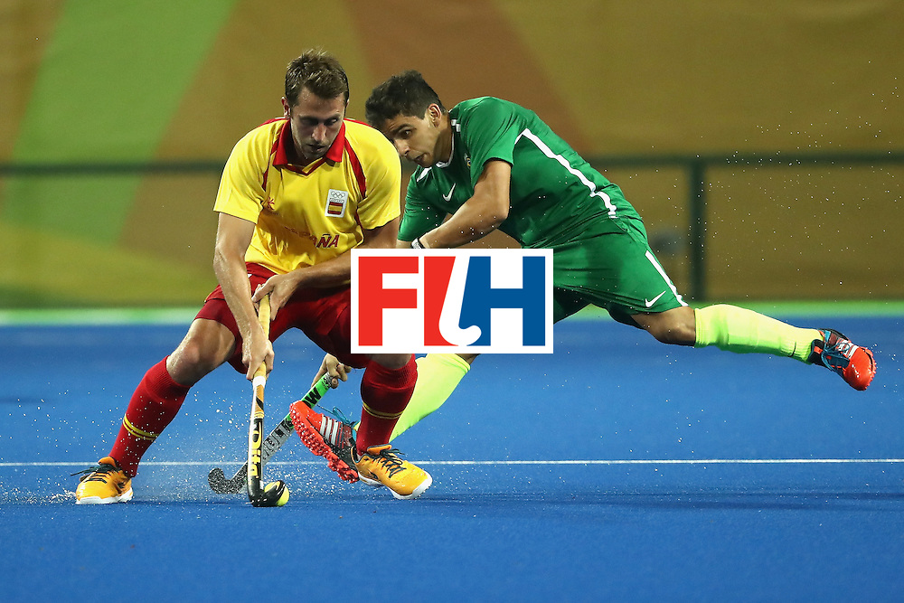 RIO DE JANEIRO, BRAZIL - AUGUST 06:  Roc Oliva #11 of Spain avoids Joaquin Lopez #5 of Brazil during a Men's Pool A match between Brazil and Spain on Day 1 of the Rio 2016 Olympic Games at the Olympic Hockey Centre on August 6, 2016 in Rio de Janeiro, Brazil.  (Photo by Sean M. Haffey/Getty Images)