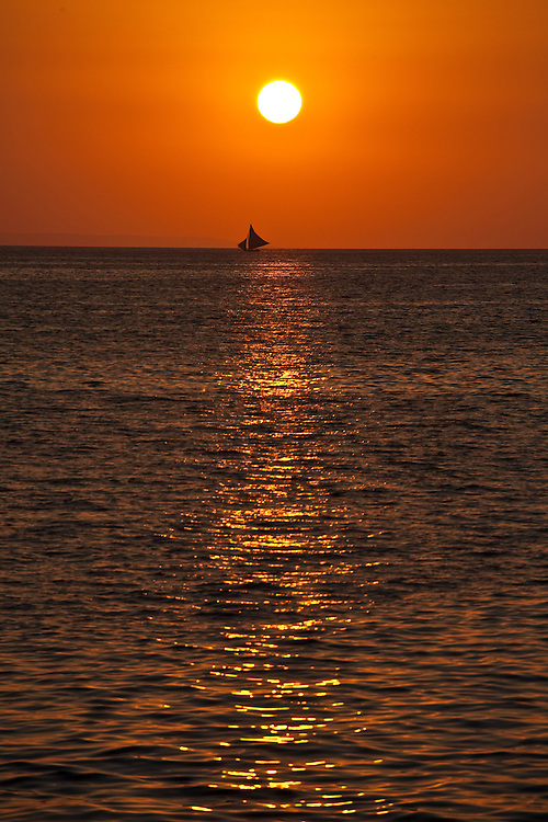 A boat floats on the horizon silhouetting against a sunset off the Coast of Haiti
