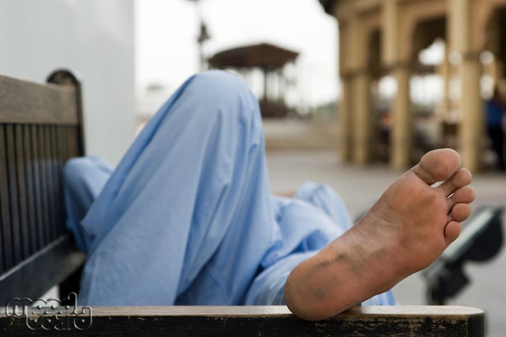 Dubai UAE man taking rest on park bench along boardwalk in Bur Dubai
