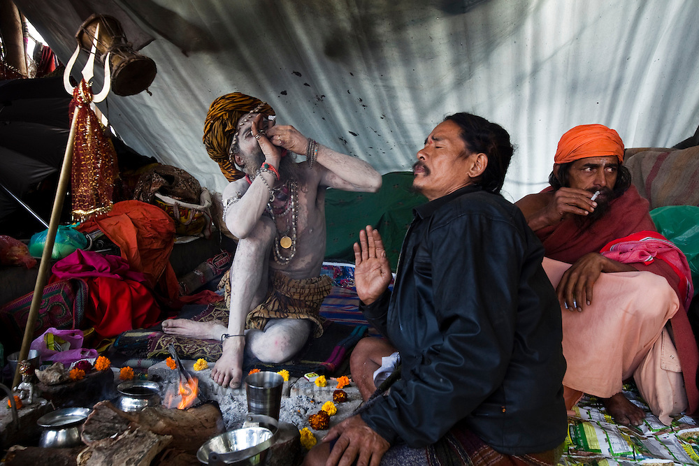 A Naga sadhu (L) smokes a chillum ( traditional smoking pipe) while another sadhu (far right) smokes a Classic Milds in their tent during the Maha Kumbh ceremony in Haridwar, February 10, 2010.  Photographer:Prashanth Vishwanathan