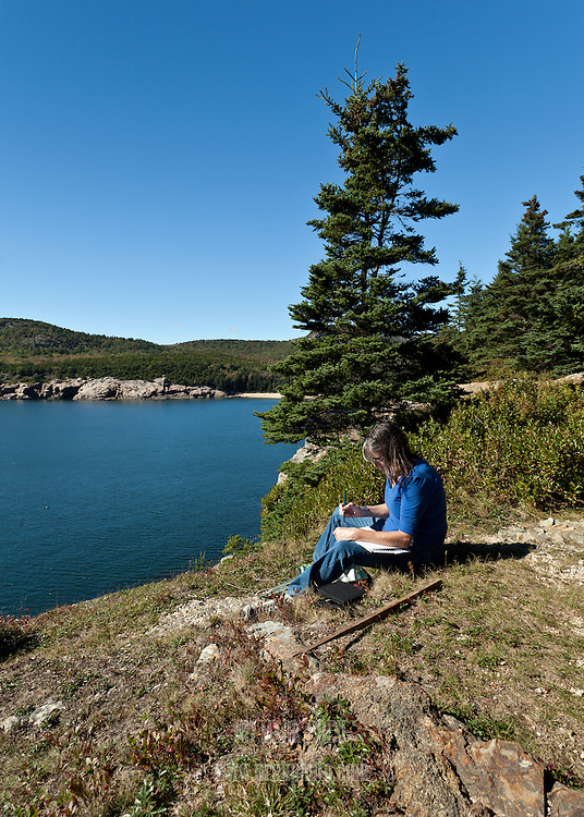 A watercolor artist sitting at the edge of the Great Head trail in Acadia National Park.