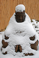 A seated Buddha statue in a blanket of snow.