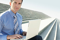 Young businessman sitting on steps using laptop portrait.