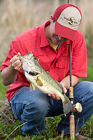 ANGLER ON A FARM POND USING A BAITCASTING RIG AND HOLDING A LARGEMOUTH BASS