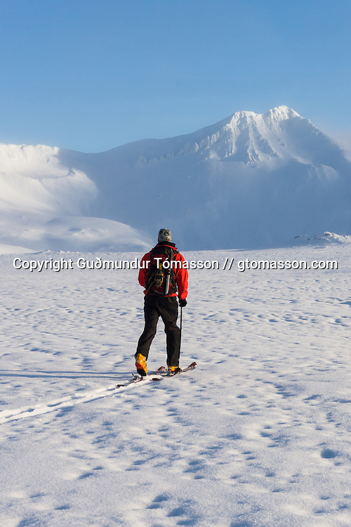 Arnar Felix Einarsson walking on skis towards mt. Hornklofi. Tindfjöll mountain range, Iceland.