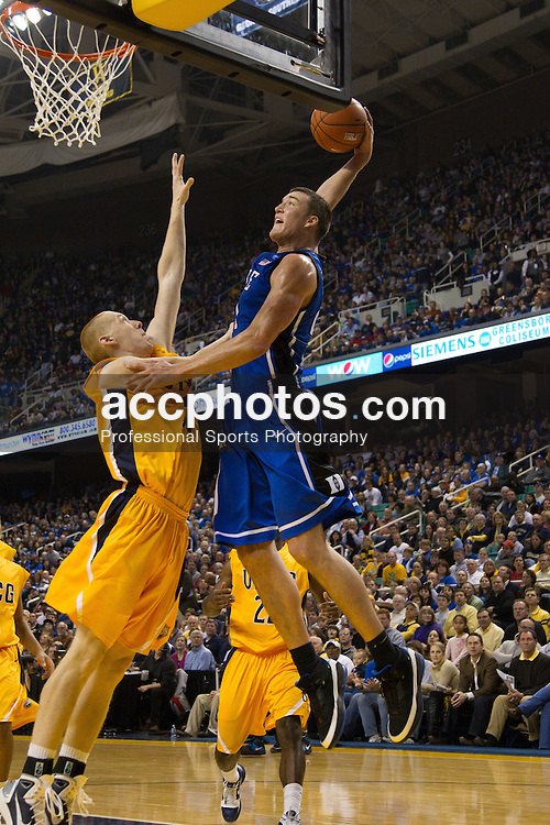 GREENSBORO, NC - DECEMBER 29: Miles Plumlee #21 of the Duke Blue Devils jumps to slam dunk the ball over Brian Cole #50 of the UNC-Greensboro Spartans on December 29, 2010 at the Greensboro Coliseum in Greensboro, North Carolina. Duke won 108-62. (Photo by Peyton Williams/Getty Images) *** Local Caption *** Miles Plumlee;Brian Cole