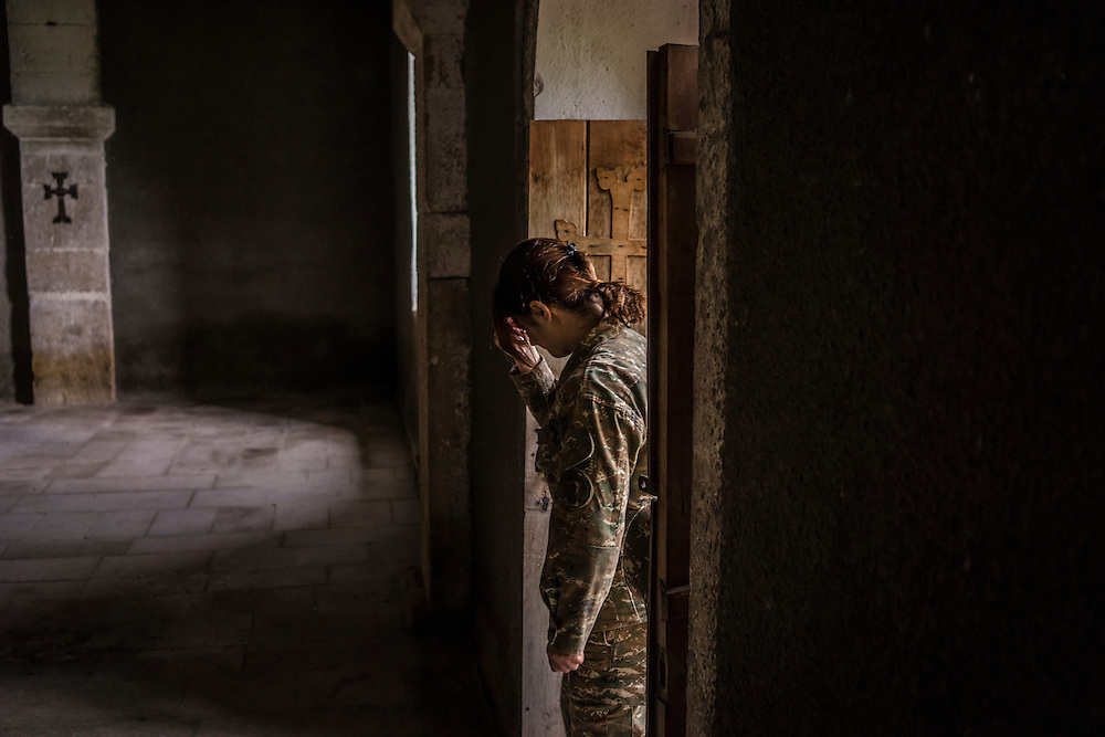 A female fighter with the Nagorno-Karabakh armed forces crosses herself while leaving a service at the Church of Mother Mary on Sunday, May 8, 2016 in Talish, Nagorno-Karabakh. Due to intense nearby fighting in early April, the entire village has been evacuated of civilians.