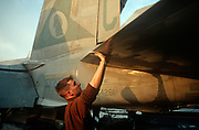 A US Navy crewman cleans the underside of flight-critical surfaces on the deck of US Navy aircraft carrier USS Harry S Truman during its deployment patrol of the no-fly zone at an unknown location in the Persian Gulf, on 8th May 2000, in the Persian Gulf. The Truman is the largest and newest of the US Navy's fleet of new generation carriers, a 97,000 ton floating city with a crew of 5,137, 650 are women. (Photo by Richard Baker / In Pictures via Getty Images)