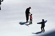 father helping his daughter to learn ice skating