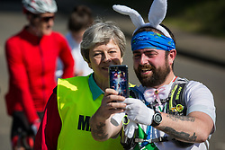 Maidenhead, UK. 19th April, 2019. A runner wearing rabbit ears takes a selfie with Prime Minister Theresa May as she serves as a marshal at the annual Maidenhead Easter 10 charity race on Good Friday.