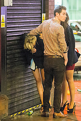 © Licensed to London News Pictures . 01/01/2015 . Manchester , UK . A man holds up a woman's hair as she bends over , outside a restaurant on Deansgate . Revellers usher in the New Year on a night out in Manchester City Centre .  Photo credit : Joel Goodman/LNP