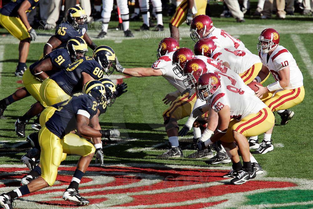 1 January 2007:  Quarterback John David Booty calls plays infront of his offensive line at the line of scrimmage at the 93rd Rose Bowl Game at the Rose Bowl Stadium for the Pac-10 USC Trojans vs the Big-10 Michigan Wolverines NCAA college football game in Southern California.  Trojans defeated the Wolverines 32-18 in regulation. #67 Ryan Kalil pushes off with his hands on the helmet of Alan Branch.<br />