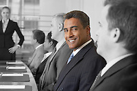 Portrait of smiling businessman in conference room with colleagues