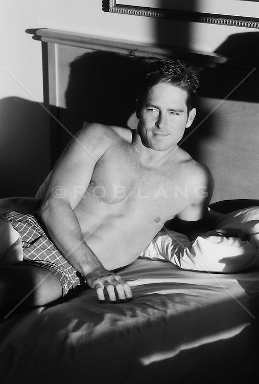 Shirtless man in bed