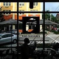 ST. PETERSBURG, FL -- July 01, 2008 -- Bob Devin Jones, artistic director of The Studio@620 gallery, does some morning business over a cup of coffee at the Kahwa Coffee Roasting espresso bar in downtown St. Petersburg, Fla., stand for a portrait outside of their cafe on Tuesday, July 01, 2008.  St. Petersburg's downtown is thriving with new shops, restaurants, and bars that are feeding off a younger, energetic crowd that fills its walkable map pinpointed with rejuvenated historic hotels and condos.