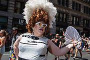 New York, NY - 30 June 2019. The New York City Heritage of Pride March filled Fifth Avenue for hours with participants from the LGBTQ community and it's supporters. A man wears a white dress and feathered hat.