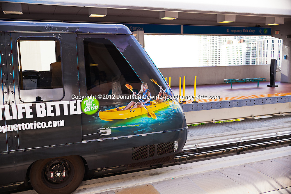 An automated rail car with a vivid photographic advertisement on its exterior departs a downtown Miami Metromover station. WATERMARKS WILL NOT APPEAR ON PRINTS OR LICENSED IMAGES.