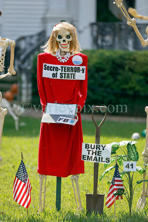 30 October 2015. New Orleans, Louisiana.<br /> The Skeleton Krewe mansion on St Charles Avenue at the corner of State Street draws crowds with its satirically spooky Halloween decorations. American politics comes under fire with skeletons depicting Presidential hopeful Hillary Clinton as 'Secre-Terror-y of State' with her buried e-mails.<br /> Photo©; Charlie Varley/varleypix.com