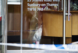 "© London News Pictures. 07/05/2013. Sunbury-On-Thames, UK. Evidence bags inside Chelsea Building Society in Sunbury-on-Thames, in Surrey, which was robbed earlier today (Wed). 55-year-old escaped prisoner Michael Wheatley AKA ""Skull Cracker"", who was arrested in east London, is alleged to have carried out the robbery. Photo credit: Ben Cawthra/LNP"