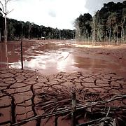 Brasile, Amazzonia, garimpo de Juma. Le miniere a cielo aperto del garimpo de Juma, dove la vita dei minatori scorre tra pericolo per un lavoro al limite e deforestazione incontrollata. Aspettando di trovare l'oro che cambi la loro vita. In questa foto il paesaggio deturpato da anni di sfruttamento incontrollato del territorio. Brazil, Amazonia, garimpo de Juma. The open pit mines of garimpo de Juma, where the miners work flows between danger and uncontrolled deforestation. Waiting to find the gold that changes their lives. In this picture the landscape scarred by years of uncontrolled exploitation of the territory.