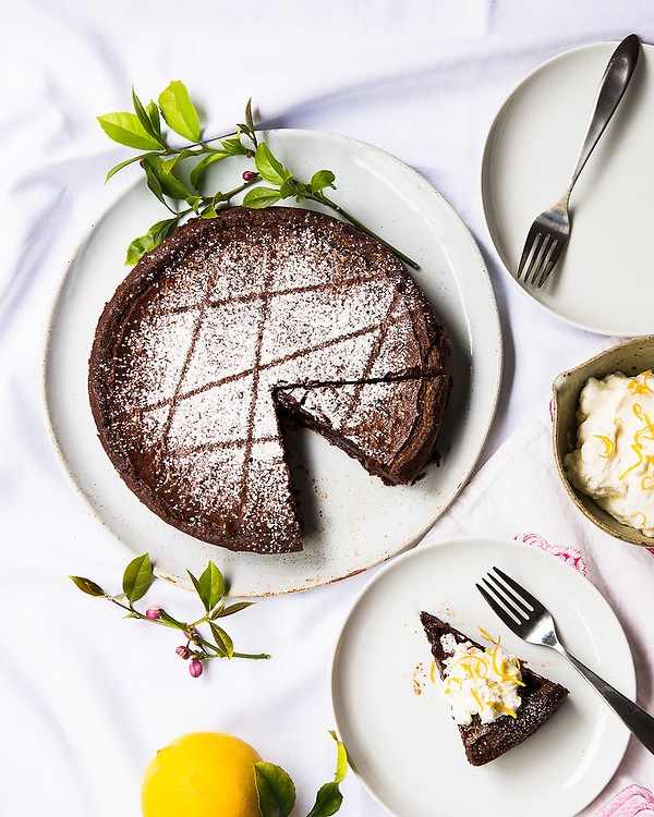 Flourless chocolate cake served in slices with lemon whipped cream
