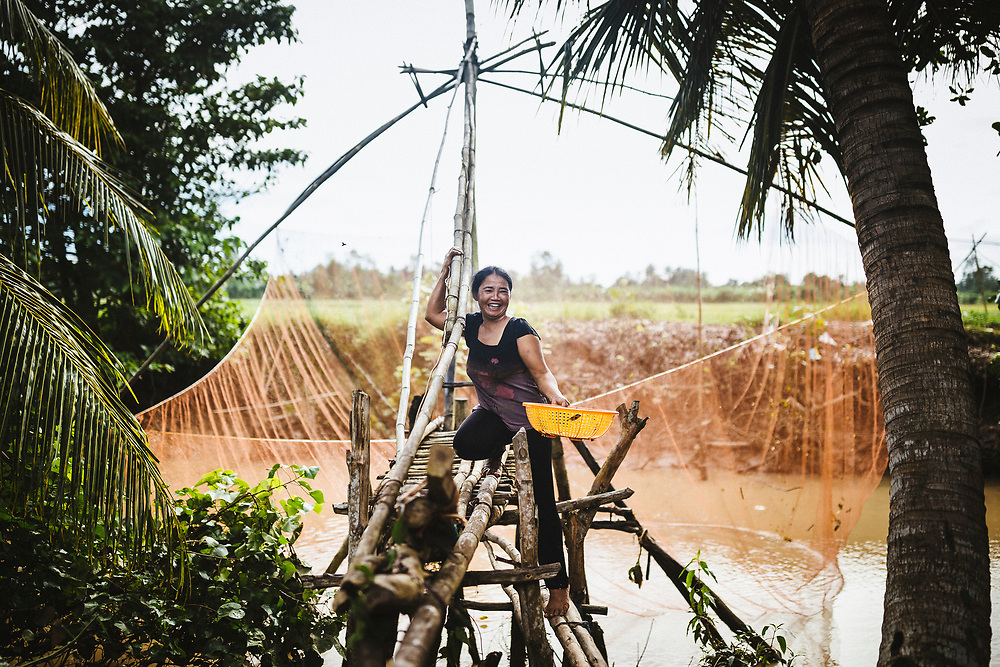 A woman collects small fish from a tributary running through a village in the Mekong Delta, in southern Vietnam.