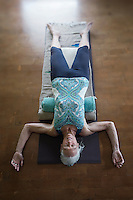 Restorative Yoga with blankets and a bolster.<br />