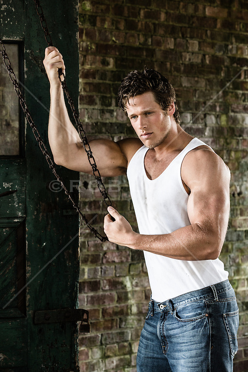 muscular man in a tank top holding a chain in an abandoned building