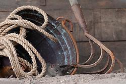 Bruine rat tussen oud tuingereedschap;