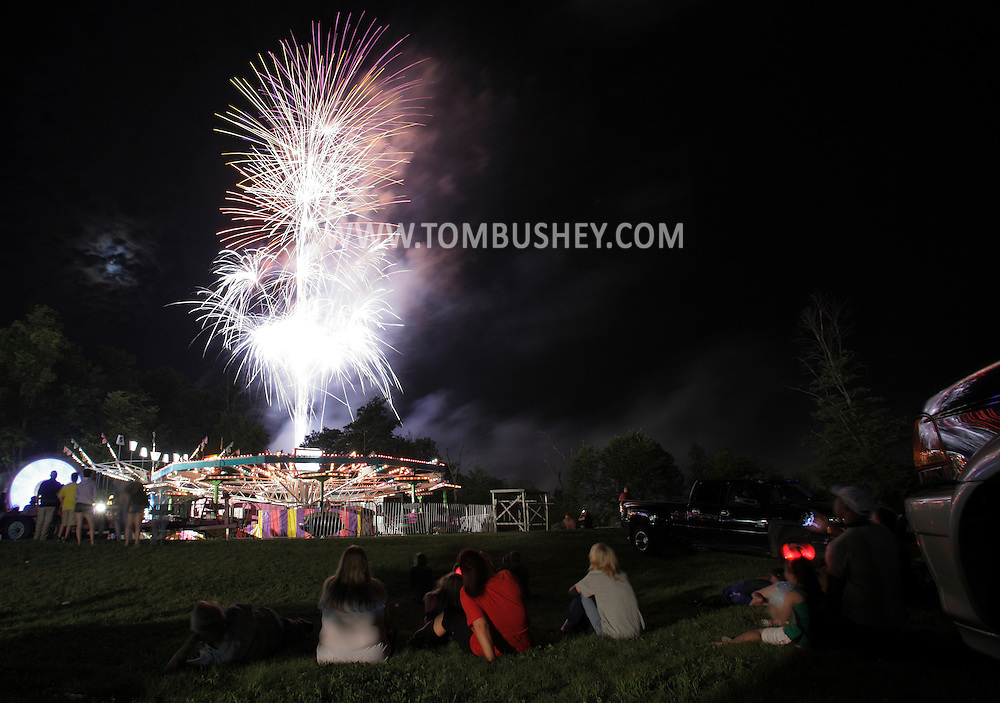 Pine Bush, New York - People watch the fireworks explode over rides at a firemen's fair the night of June 19, 2010.