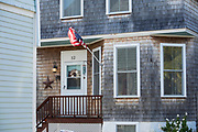 Typical traditional wooden cedar shingles house with patriotic Stars and Stripes flag in Newport, Rhode Island, USA