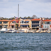 Photo of Orange County waterfront homes in Newport Beach along  Newport Harbor. Newport Beach is a wealthy beach city along the Pacific Ocean in Orange County Southern California.