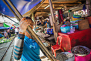 17 JANUARY 2013 - SAMUT SONGKHRAM, SAMUT SONGKHRAM, THAILAND: A market vendor picks up the awning from her market stall as a train comes into the market in Samut Songkhram. Four trains each day make the round trip from Baan Laem, near Samut Sakhon, to Samut Songkhram, the train chugs through market eight times a day (coming and going). Each time market vendors pick up their merchandise and clear the track for the train, only to set up again when the train passes. The market on the train tracks has become a tourist attraction in this part of Thailand and many tourists stop to see the train on their way to or from the floating market in Damnoen Saduak.    PHOTO BY JACK KURTZ