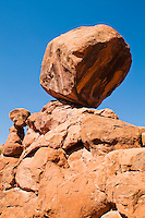 A large boulder leaning precariously on a slanted rock formation in The Fiery Furnace in Arches National Park, Utah, USA.