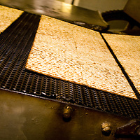 Making Kosher for Passover matzoh at Streit's Matzoh, Lower East Side, NYC. The matzoh emerges from the oven, where it has cooked for one minute and 40 seconds at 800 degrees. By Jewish law, to keep matzoh fit for use during Passover one must complete the entire matzoh-making process - from the time the grain comes into contact with the water up to and including the completion of the baking of the matzoh - within 18 minutes.