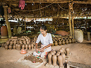 30 OCTOBER 2015 - TWANTE, MYANMAR: A woman trims excess clay off pots in a shed in the potters' village in Twante, (also spelled Twantay) Myanmar. Twante, about 20 miles from Yangon, is best known for its traditional pottery. The pottery makers are struggling to keep workers in their sheds though. As Myanmar opens up to outside investments and its economy expands, young people are moving to Yangon to take jobs in the better paying tourist industry or in the factories that are springing up around Yangon.     PHOTO BY JACK KURTZ